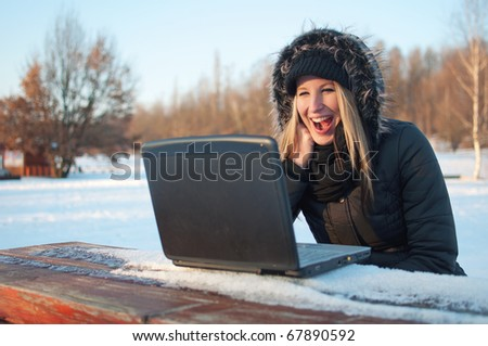 Smiling beautiful young woman with laptop sitting on a bench in winter surrounded by snow - stock photo