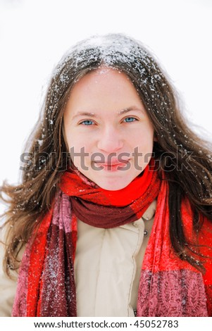 Smiling beautiful young woman with long brown hair in snow, outside on snowy day
