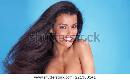 Smiling beautiful young woman with long healthy hair looking at camera. - stock photo