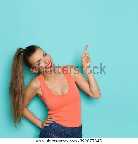 Smiling beautiful young woman with ponytail pointing up at copy space. Waist up studio shot on teal background. - stock photo