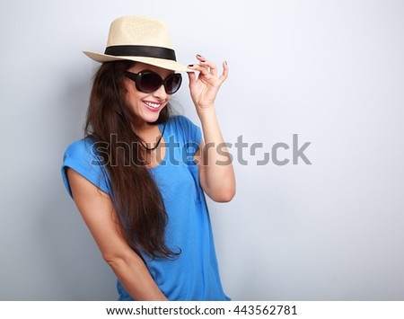 Smiling beautiful young woman with straw hat and fashion sun glasses on blue background with empty copy space