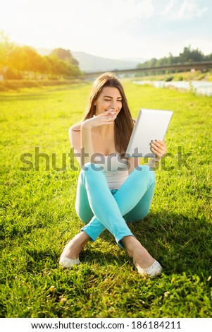 Smiling beautiful young woman with tablet computer sitting on grass in nature on sunny summer day. People and technology. Modern lifestyle. Relaxation and fun concept.