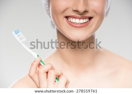 Smiling beautiful young woman with towel on head using toothbrush. - stock photo