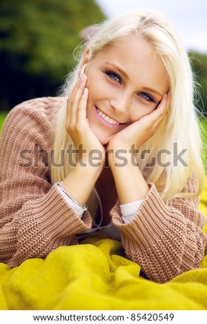 Smiling beauty lying on a blanket - stock photo