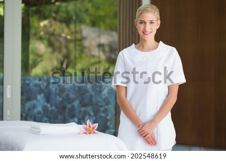 Smiling beauty therapist standing beside massage towel at the spa - stock photo