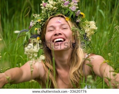 smiling beauty woman with flowers on meadow - stock photo