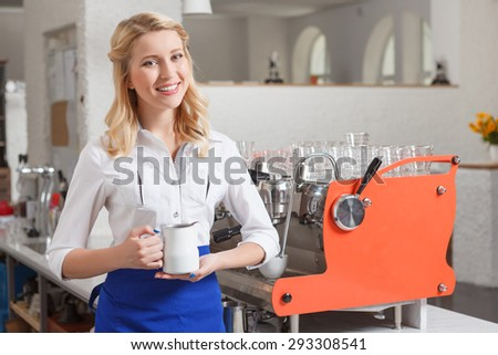 Smiling beauty. Young blond-haired female barista standing in coffee shop with milk jar