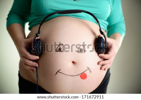 Smiling belly of a pregnant woman listens to music through headphones - stock photo