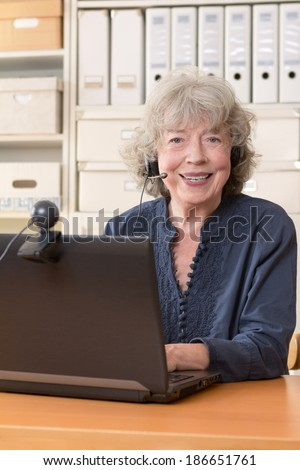 Smiling best ager with laptop, camera and headset, copy space - stock photo
