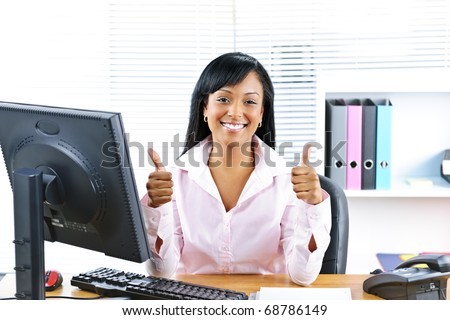 Smiling black business woman giving thumbs up gesture at desk in office - stock photo