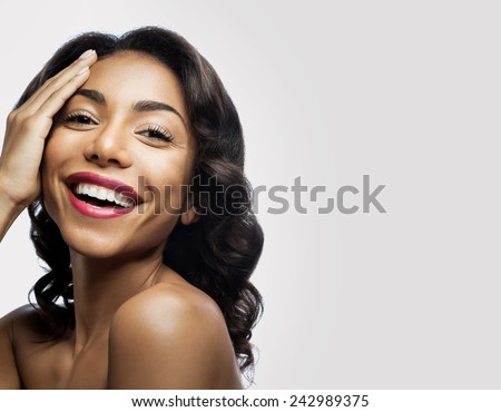 Smiling black girl with perfect healthy skin and makeup. As for the hand of his face on a gray background - stock photo