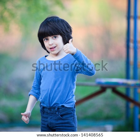 smiling black-haired boy in blue shirt showing a thumbs up - stock photo