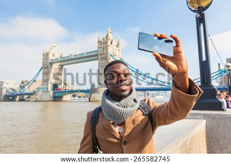 Smiling black man taking selfie in London with Tower Bridge on background. He is holding the phone and looking at camera. Photo taken on a sunny winter day. - stock photo