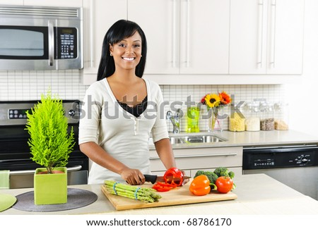Smiling black woman cutting vegetables in modern kitchen interior - stock photo