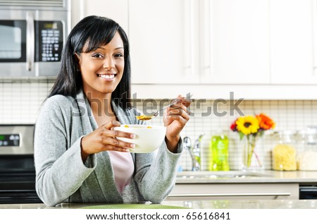 Smiling black woman having breakfast in modern kitchen interior