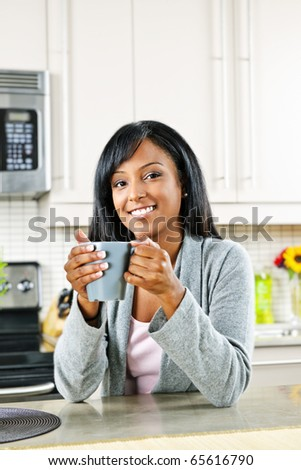 Smiling black woman holding coffee cup in modern kitchen interior - stock photo