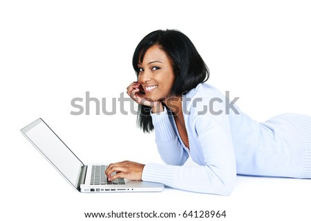Smiling black woman using computer laying on floor looking at camera - stock photo