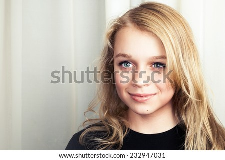 Smiling blond Caucasian girl, closeup studio portrait - stock photo