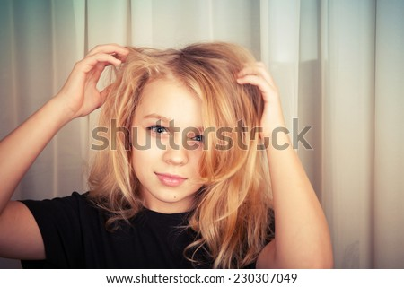 Smiling blond Caucasian girl with disheveled hair, closeup studio portrait - stock photo