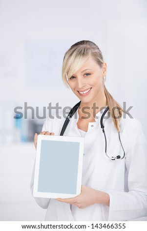 Smiling blond doctor with stethoscope shows the digital tablet