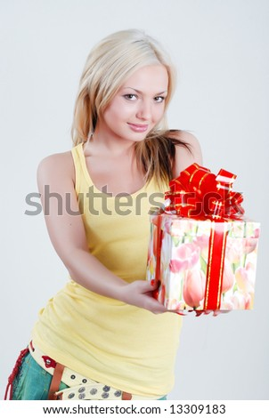 Smiling blond dressed in yellow shirt with big gift box in hands