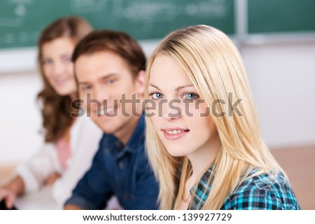 Smiling blond female college student in a classroom - stock photo