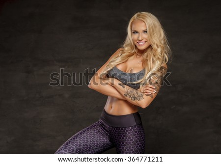 Smiling blond fitness woman in colorful sportswear. - stock photo