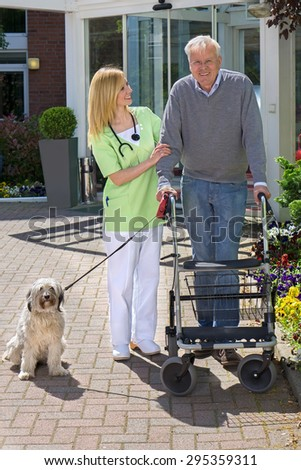 Smiling Blond Nurse Holding onto Arm of Senior Man  Helping Man with Walker Walk Dog on Leash Outdoors in front of Retirement Building on Sunny Day. - stock photo