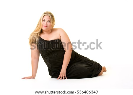 Smiling blond overweight woman in black dress relaxing on white background