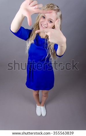 Smiling blond teen girl looking at the camera through hands.  Blue short dress , white sneakers , gray background