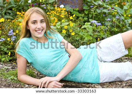Smiling blond teenage girl lying on ground resting on elbow in front of yellow flowers.