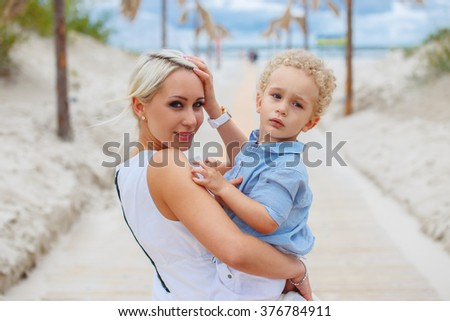 Smiling blond woman and her child on a road to the beach. - stock photo