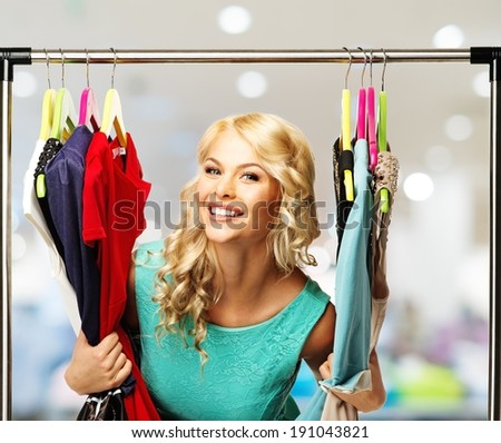 Smiling blond woman choosing clothes on a rack in a shopping mall   - stock photo