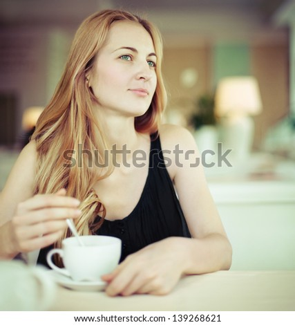 Smiling blond woman drinking coffee in cafe