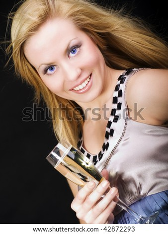 smiling blond woman holding champagne and celebrating - stock photo