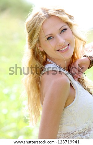 Smiling blond woman in meadow during summer - stock photo