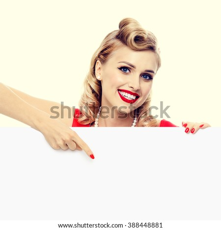 smiling blond woman in pin-up style dress, showing blank signboard with copyspace. Caucasian blond model posing in retro fashion and vintage concept studio shoot.