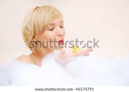 Smiling blond woman lying in bubble bath with toy duck - stock photo