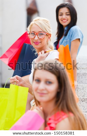 Smiling blond woman out in city shopping with her girlfriends.