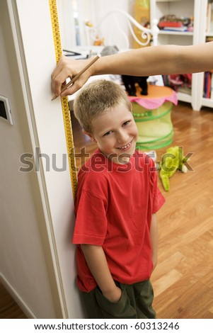 Smiling blond young boy getting height measurement in doorway - stock photo