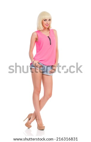 Smiling blond young woman in high heels and pink top posing with legs crossed at ankle. Full length studio shot isolated on white. - stock photo
