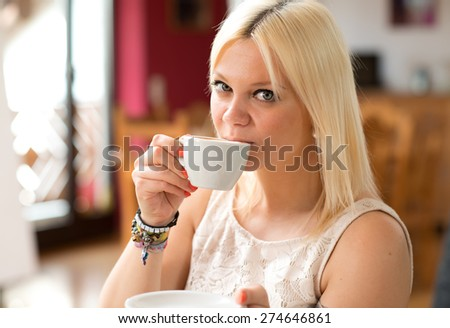 smiling blond young woman with a coffee cup in the living room