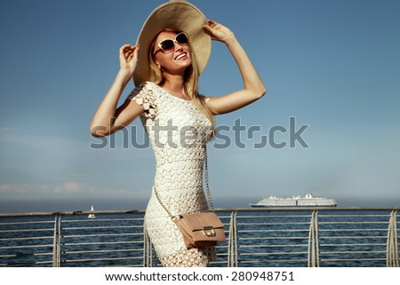 Smiling blonde attractive woman posing in sunglasses and hat. Ship on the sea on background. - stock photo