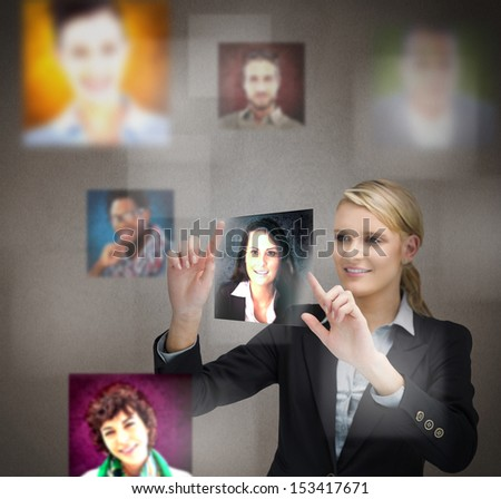 Smiling blonde businesswoman adjusting a picture on digital screen - stock photo