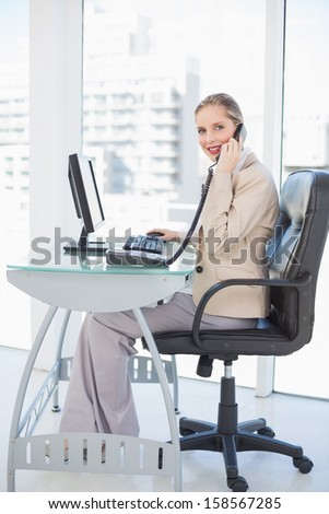 Smiling blonde businesswoman on the phone in bright office