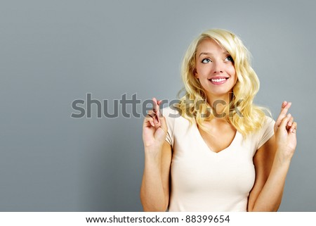 Smiling blonde caucasian woman with fingers crossed on gray background