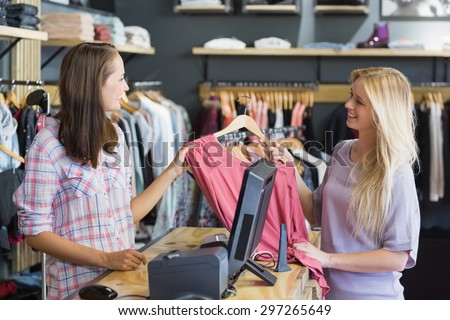 Smiling blonde doing shopping in clothes store - stock photo