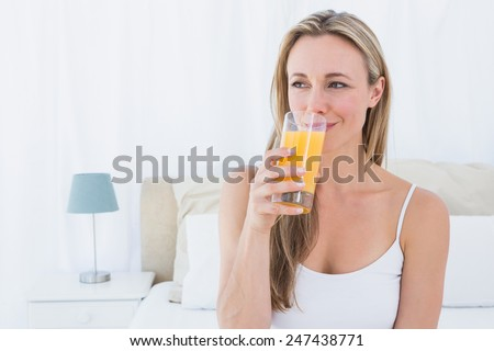 Smiling blonde drinking glass of orange juice at home in the bedroom - stock photo