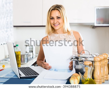 smiling blonde female signing documents at the kitchen
