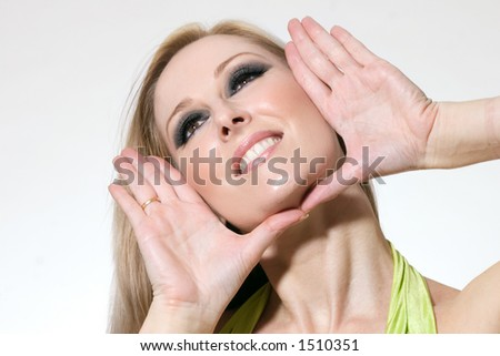 Smiling blonde female wearing makeup with hands poised in a face frame. - stock photo